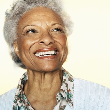 An older woman with a big beautiful smile thanks to dental bridges that are offered as part of our Hemet dental services