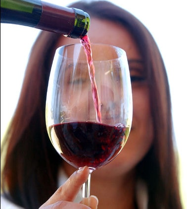 A woman holding a wine glass that is being filled