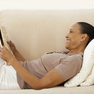 A woman reclining and reading the newspaper, in a relaxed state because of sedation dentistry which is offered as part of our Hemet dental services.