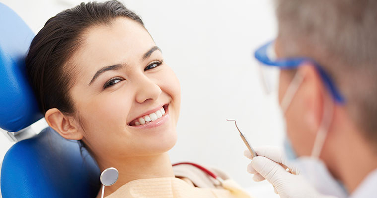Woman calm and smiling at dentist having solved dental anxiety problems with sedation dentistry